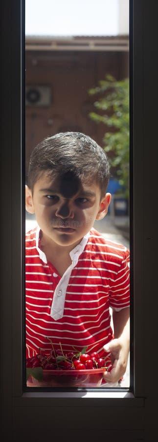 小男孩身分外部用碗樱桃和看通过门 童年,夏令时概念 免版税库存照片