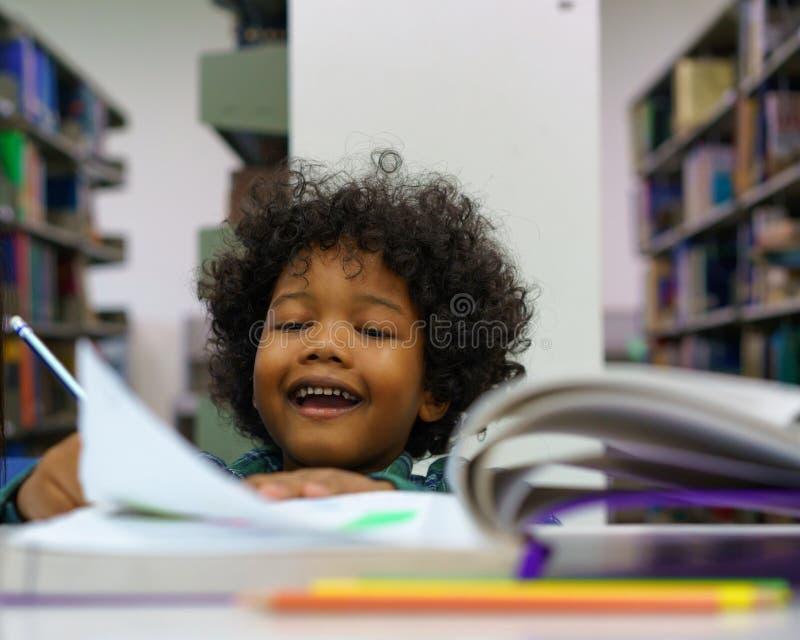 小男孩阅读书在图书馆里 库存照片