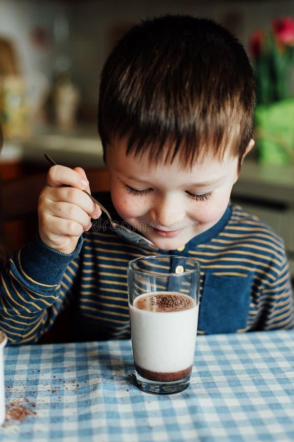 小男孩饮料牛奶和在早晨准备可可粉在厨房里 免版税库存照片