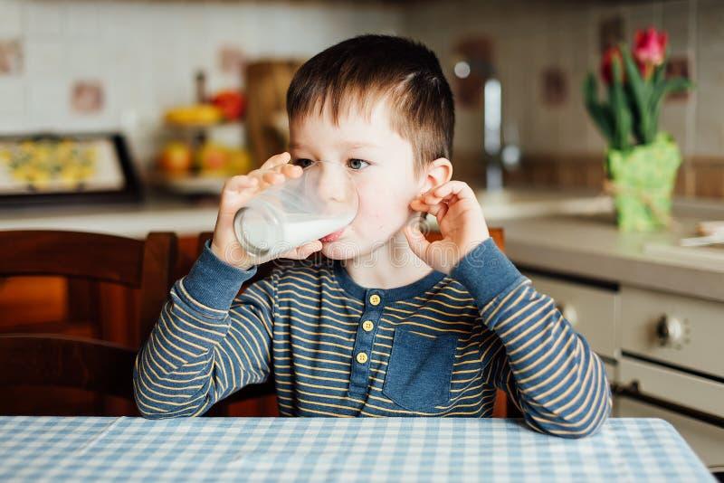 小男孩饮料牛奶在厨房里在早晨 图库摄影