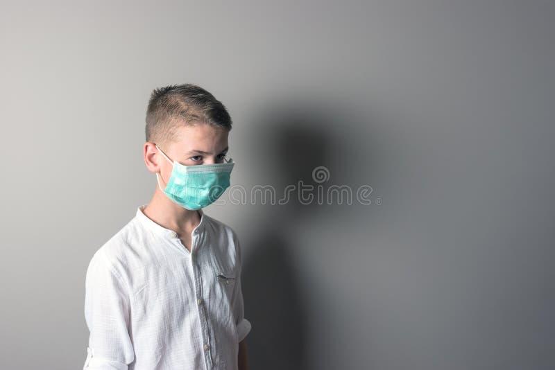 小男孩,一个医疗面具的一个孩子在明亮的背景 流行病,流行性感冒,保护的想法免受疾病, 库存图片