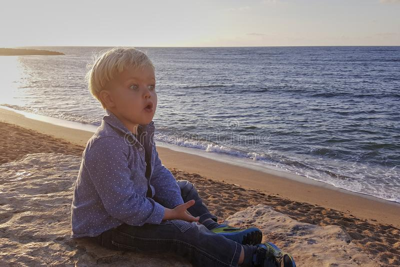 小男孩,在海附近的坐的海滩,微笑 免版税库存照片