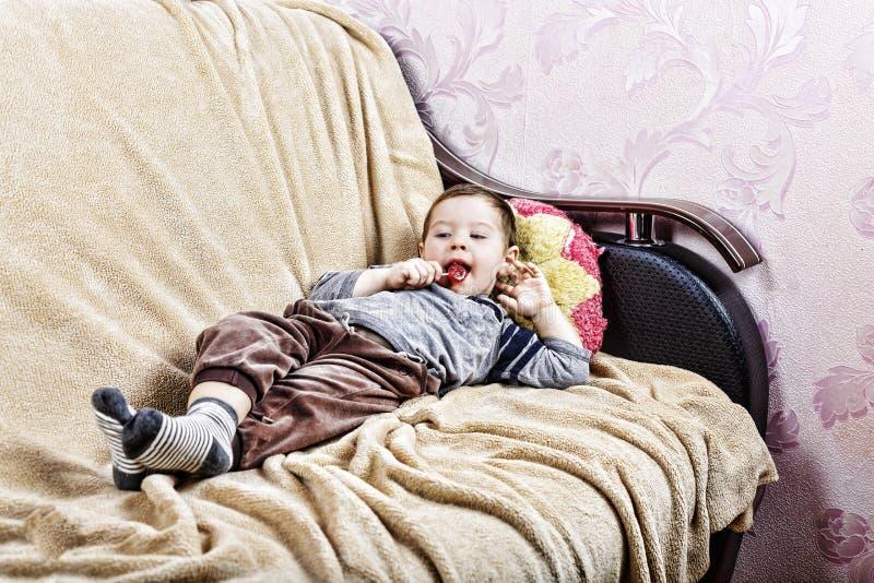 小男孩,快乐的男孩,吃棒棒糖,在家,在沙发的男孩 免版税库存图片
