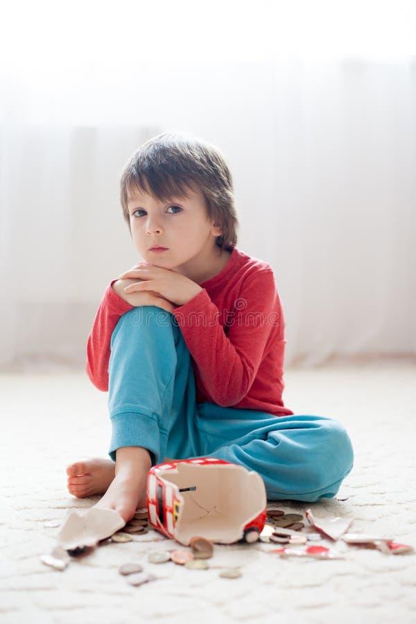 小男孩,打破他的存钱罐买礼物为母亲节 图库摄影
