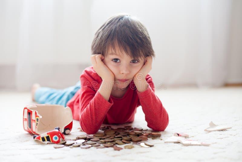 小男孩,打破他的存钱罐买礼物为母亲节 库存照片