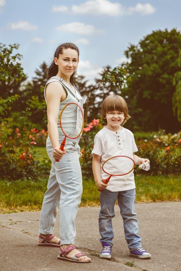 小男孩画象在拿着球拍的公园 免版税库存照片
