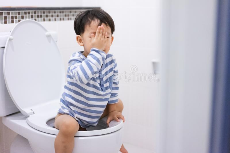 小男孩poo和小便在白色洗手间 免版税库存图片
