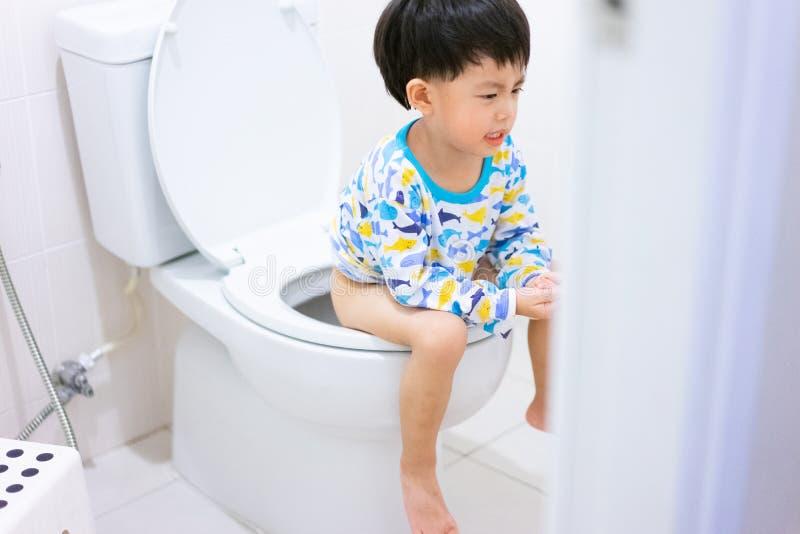 小男孩poo和小便在白色洗手间 库存图片