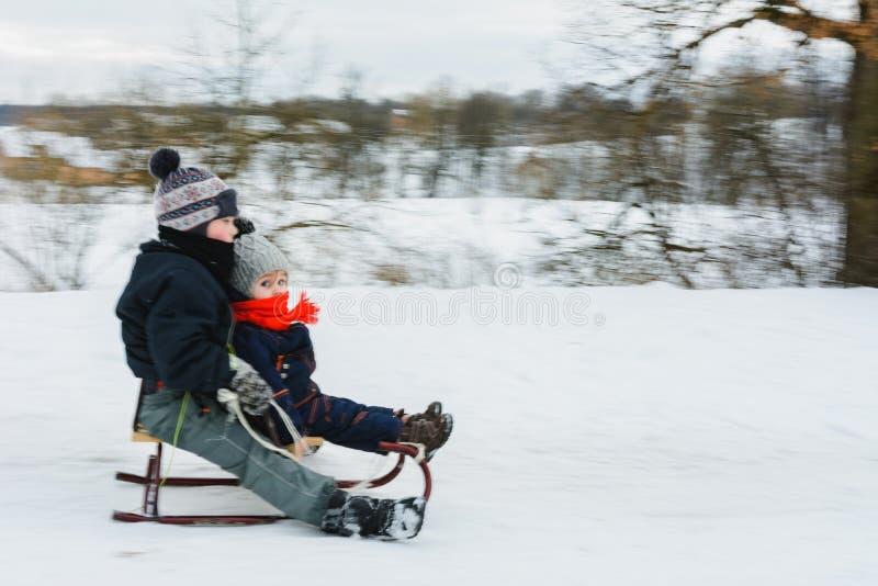 小男孩sledding在冬时 背景迷离弄脏了抓住飞碟跳的行动 免版税库存照片