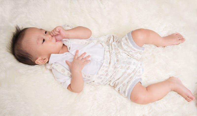 小男婴吮他的在嘴的7个月拇指手指 库存照片
