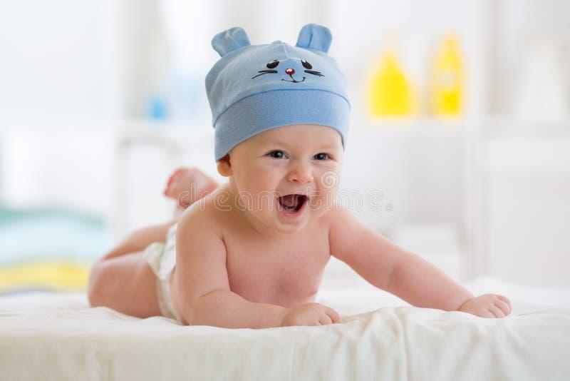 小男婴在躺下在毯子的滑稽的帽子weared 库存图片