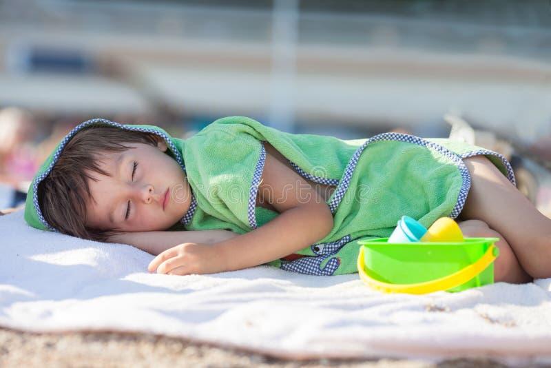 小男婴,睡觉在海滩下午 免版税图库摄影