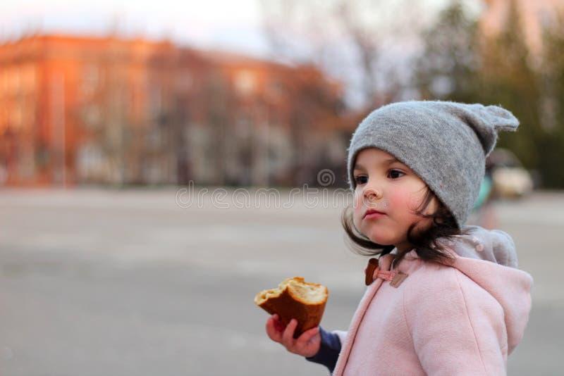 小白女孩在晚上吃在街道上的小圆面包 在日落都市风景的背景的画象 库存图片