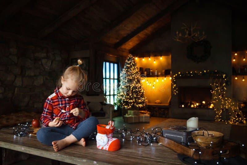 小白白肤金发的女孩坐一张木桌在瑞士山中的牧人小屋的客厅,装饰为圣诞树和诗歌选机智 免版税库存图片