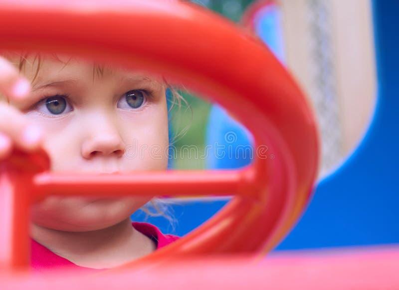小白种人女婴坐在玩具汽车的轮子 使用在操场概念 免版税图库摄影
