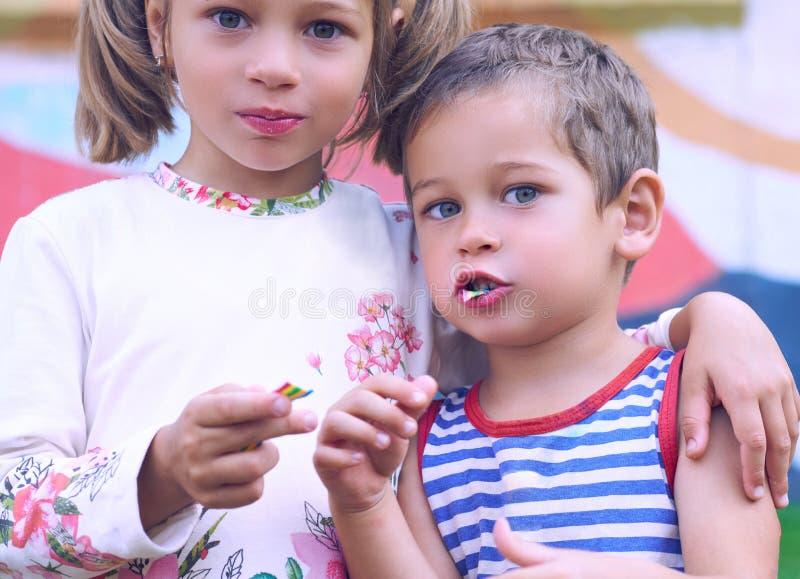小白种人男孩和女孩口香糖,当站立在胳膊时的操场胳膊 有愉快的朋友的图象 库存图片