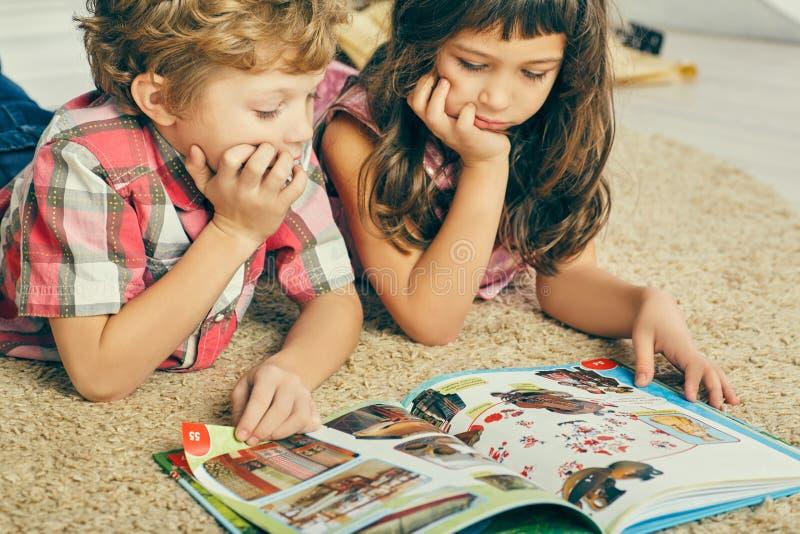 小白种人说谎在地板上和读一本图书的男孩和西班牙女孩 免版税库存图片