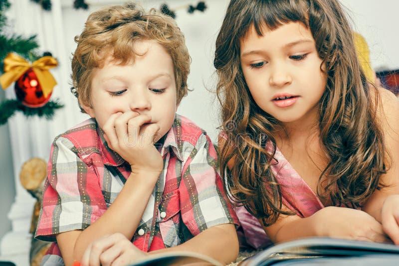 小白种人说谎在地板上在圣诞树附近和读一本图书的男孩和女孩 库存照片