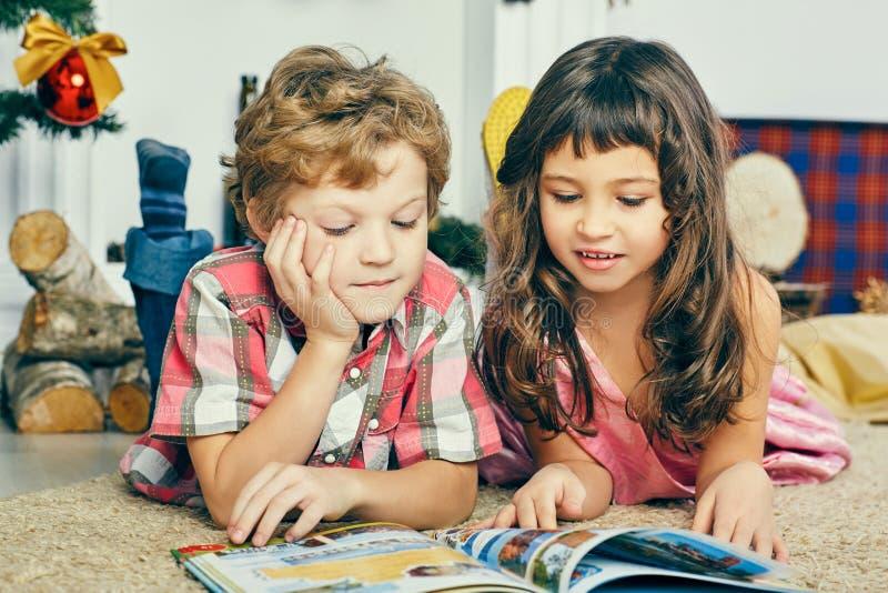 小白种人说谎在地板上在圣诞树附近和读一本图书的男孩和女孩 图库摄影