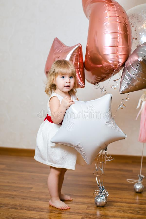 小白肤金发的女婴与大桃红色和白色气球的两岁在她的生日宴会 库存照片