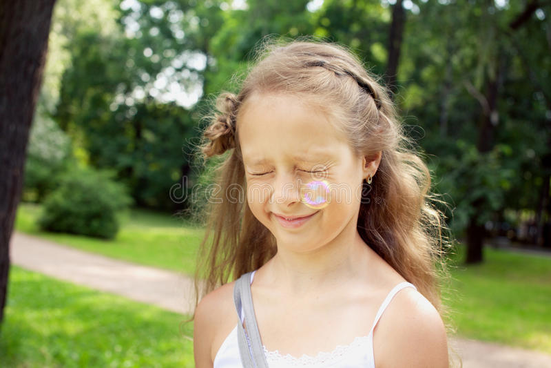 小白肤金发的女孩在公园,滑稽的女孩和肥皂泡 图库摄影