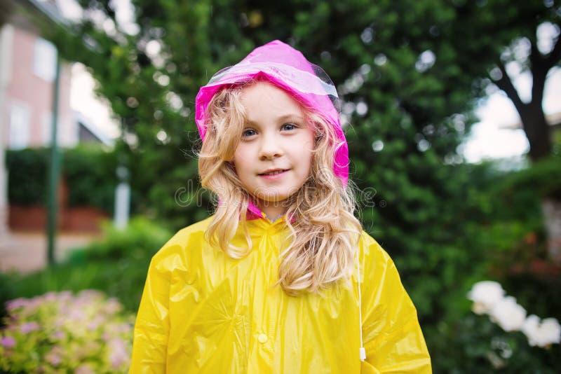 小白肤金发的女孩室外照片黄色雨衣的 免版税库存照片