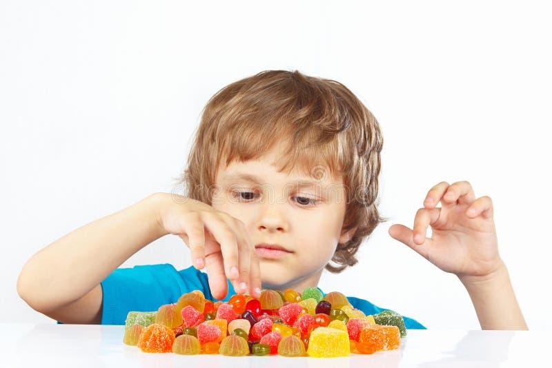 小白肤金发的孩子用在白色背景的果冻糖果 免版税库存图片