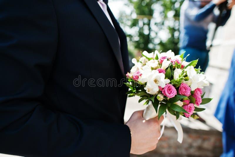小白色和玫瑰色花婚礼花束手头新郎 免版税图库摄影
