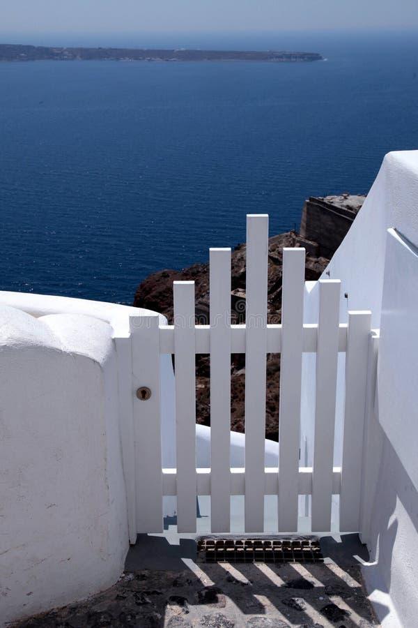 小白色篱芭门和海视图在圣托里尼海岛,希腊上 库存照片
