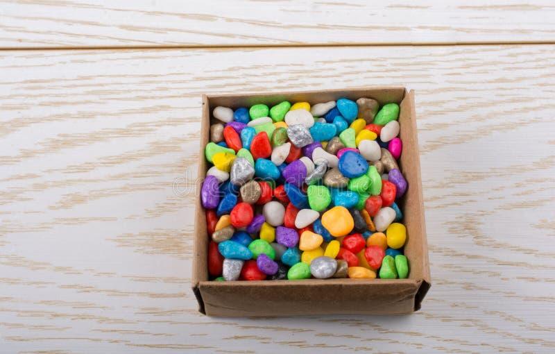 小的五颜六色的小卵石填写了一个箱子 库存图片