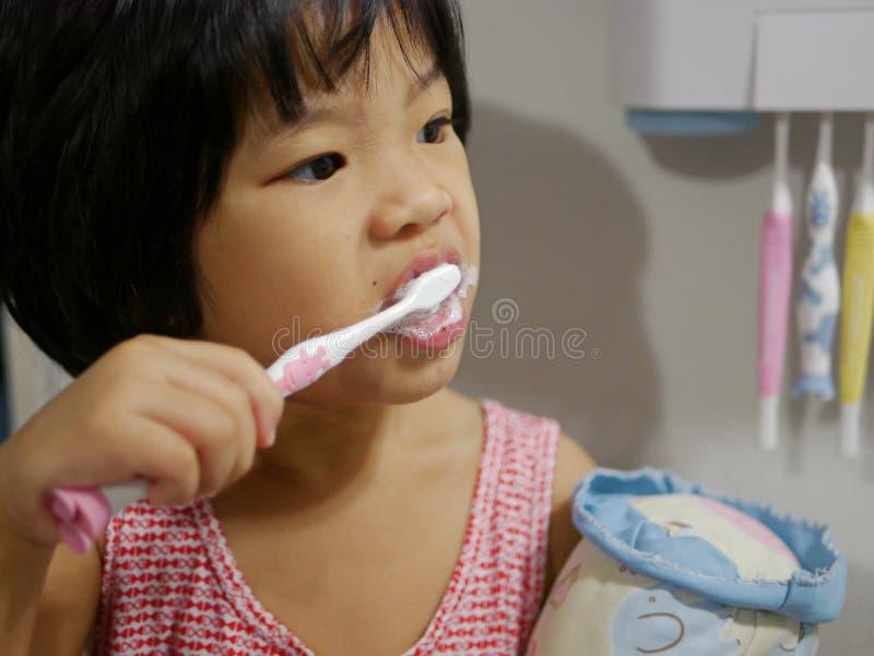 小的亚洲女婴藏品牙刷和享用刷她的牙由她自己 免版税库存照片