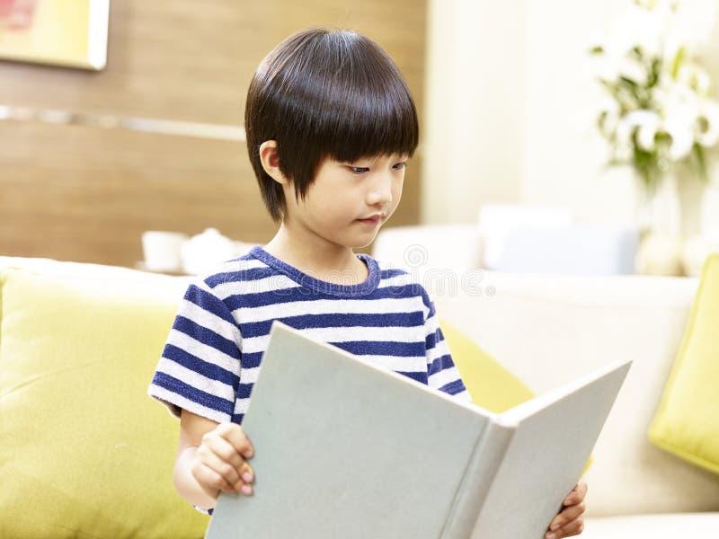 小的亚洲男孩阅读书在家 库存照片