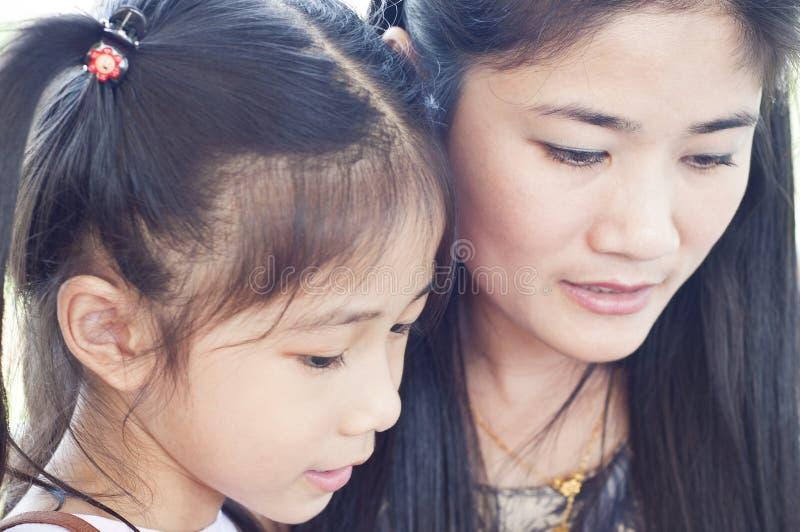 小的亚洲女孩和妈妈画象。 图库摄影
