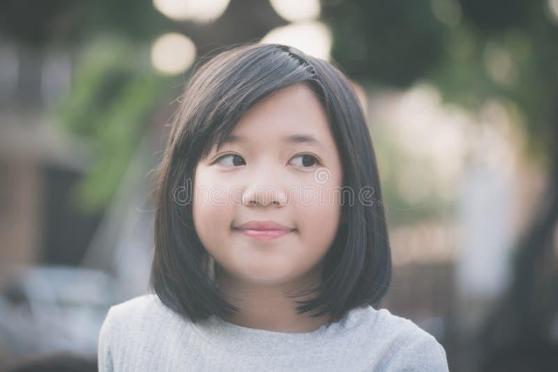 小的亚洲女孩看看边 免版税库存照片