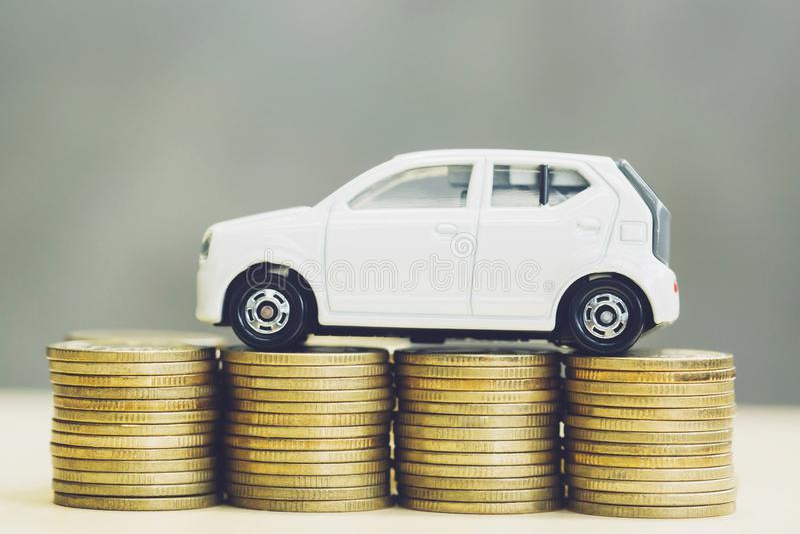 小的在很多金钱被堆积的硬币的玩具白色汽车 对银行贷款花费财务 保险,购买汽车财务 图库摄影