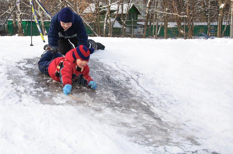 滑从小的多雪的小山的愉快的孩子 免版税库存照片