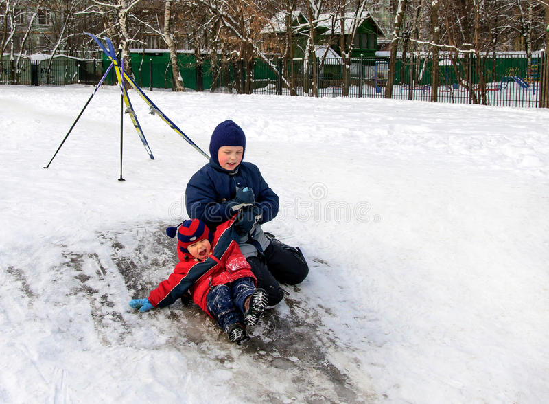 滑从小的多雪的小山的愉快的孩子 免版税库存图片
