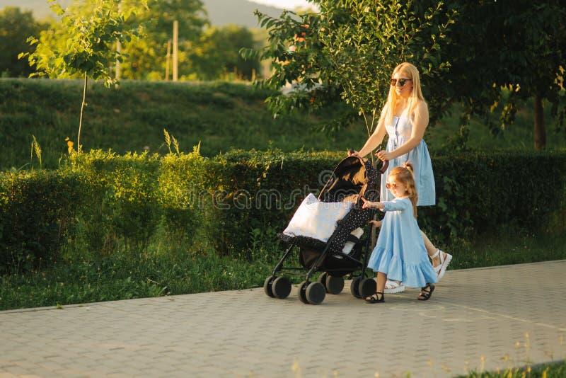 小的女儿帮助妈妈推挤婴儿车 愉快的系列 免版税图库摄影