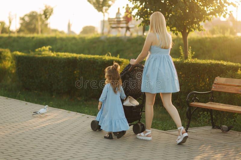 小的女儿帮助妈妈推挤婴儿车 愉快的系列 免版税库存图片