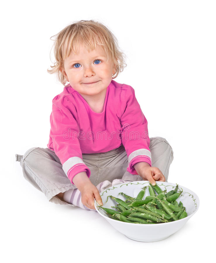 小的女孩用grean豌豆 库存照片