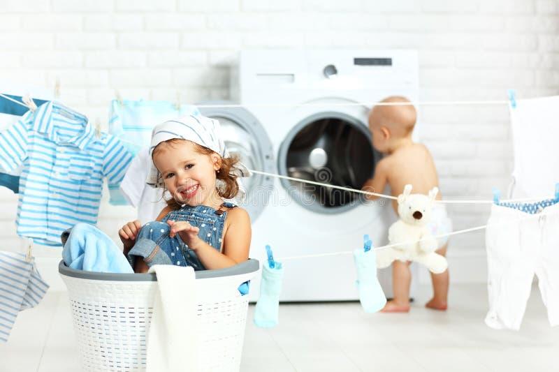 小的帮手滑稽的孩子愉快的姐妹和兄弟洗衣店的 库存图片