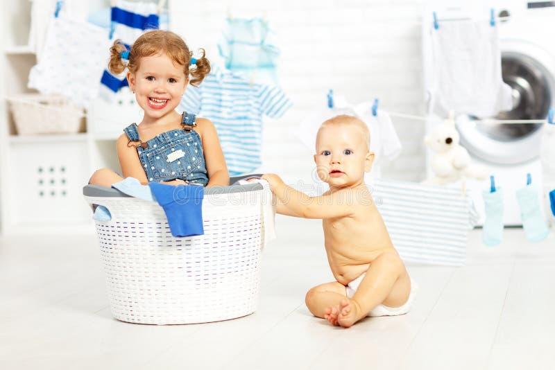 小的帮手滑稽的孩子愉快的姐妹和兄弟洗衣店的 库存照片