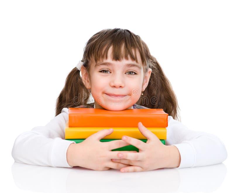 小的愉快的女孩拥抱书 背景查出的白色 免版税库存照片