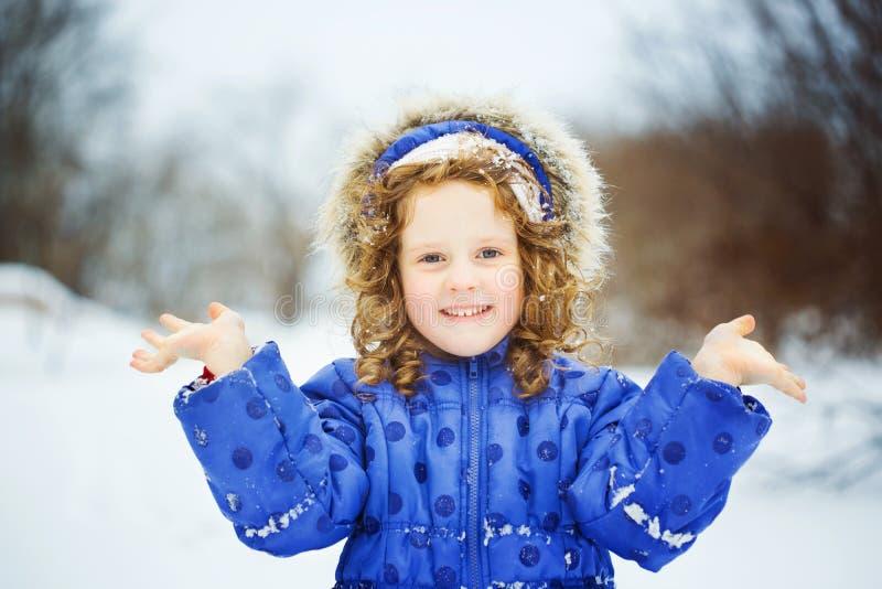 小的愉快的女孩的手和微笑 库存照片