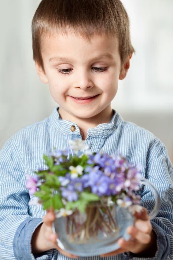 小的手,拿着有森林春天花bouqu的玻璃花瓶 免版税库存照片
