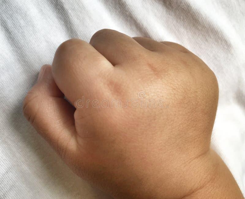 小的拳头关闭白色布料的婴儿男孩 免版税库存图片