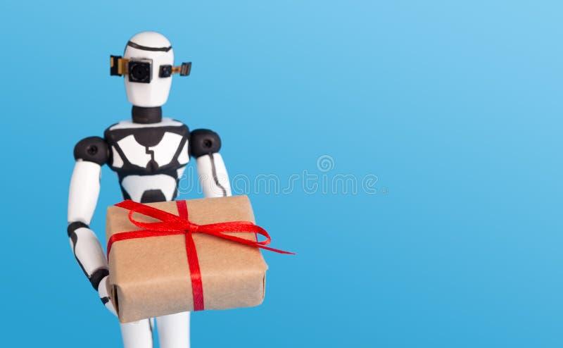 小的机器人藏品礼物盒,与空的空间的蓝色背景 库存照片