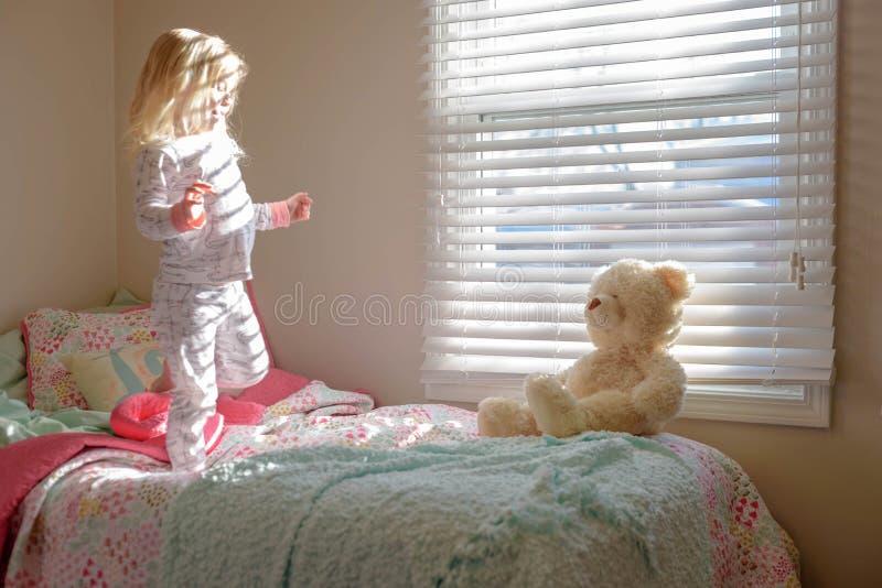 小的白肤金发的女孩和玩具熊早晨 免版税图库摄影