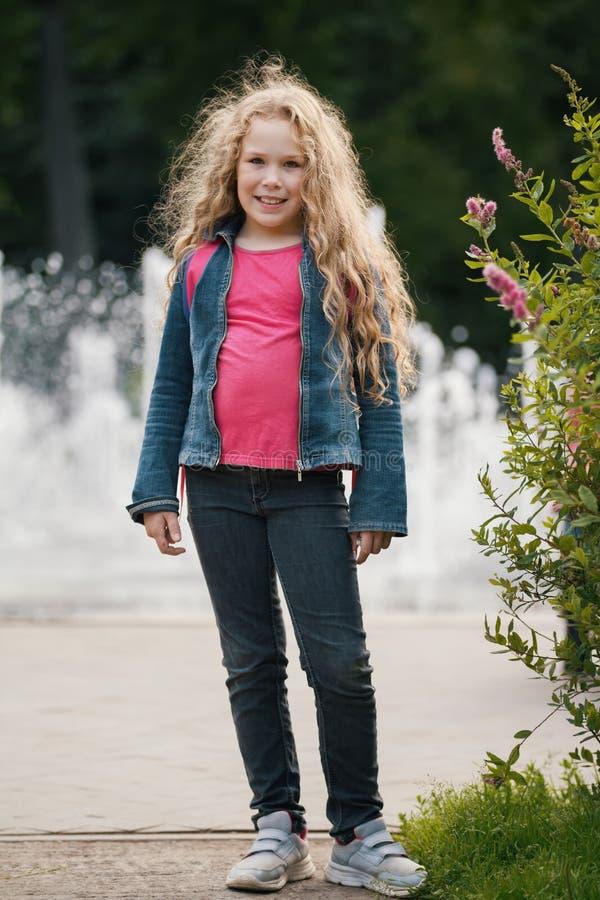 小的白肤金发的微笑的儿童佩带的牛仔裤夹克在公园 免版税库存图片