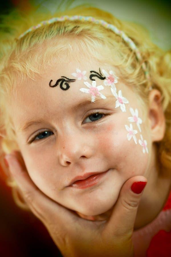 小的白肤金发的蓝眼睛的女孩面孔绘画微笑着 库存图片